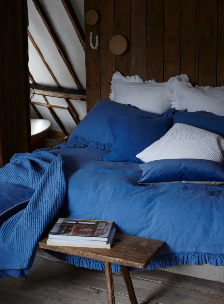 Bedlinen in blue washed denim with ruffle frill. With white linen oxford pillow cases and blue velvet cushion shot against a wooden wall. Photographed by Interior photographer Joanna Henderson based in London