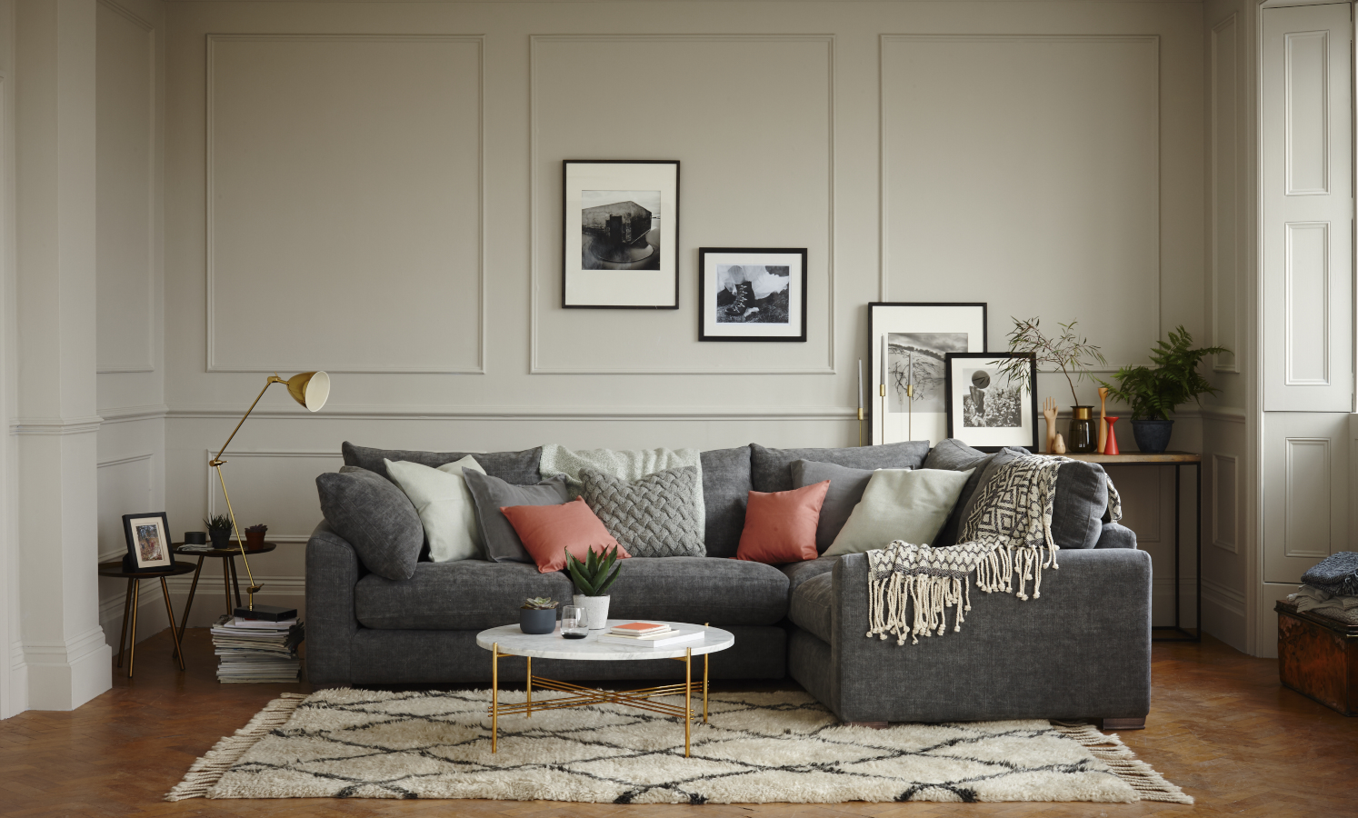 charcoal grey sofa accessorised with blush pink and grey cushions, marble coffee table and black and white prints. Interior photography by London based photographer Joanna Henderson