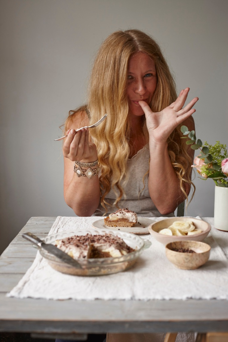 Joanna Henderson Food photography. Hanna eating banoffee pie seated at a wooden table with bananas and cocoa and fresh flowers