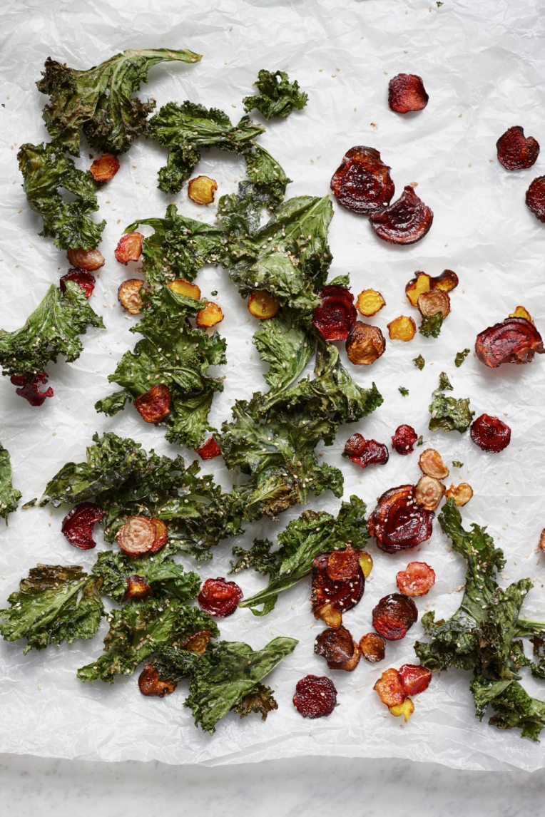 Oven roasted beetroot and kale crisps on white baking parchment. Food photography by Joanna Henderson