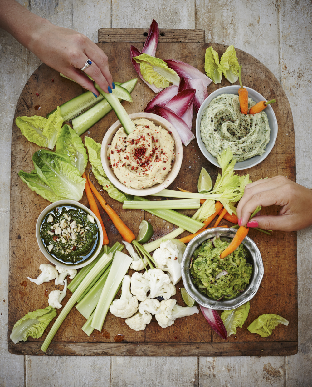 Hands reaching in to eat various dips. Food photography by London based photographer Joanna Henderson