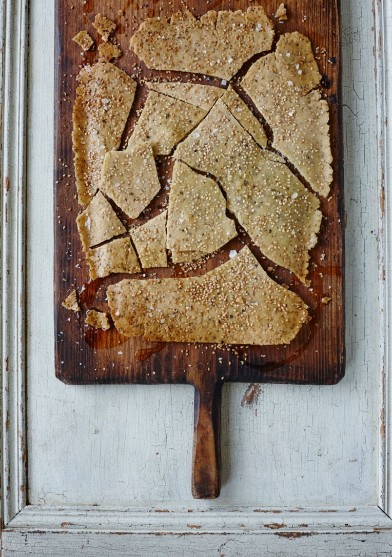 Rice snap flatbread made with sesame seeds, served on a wooden chopping board. Food photography by Joanna Henderson