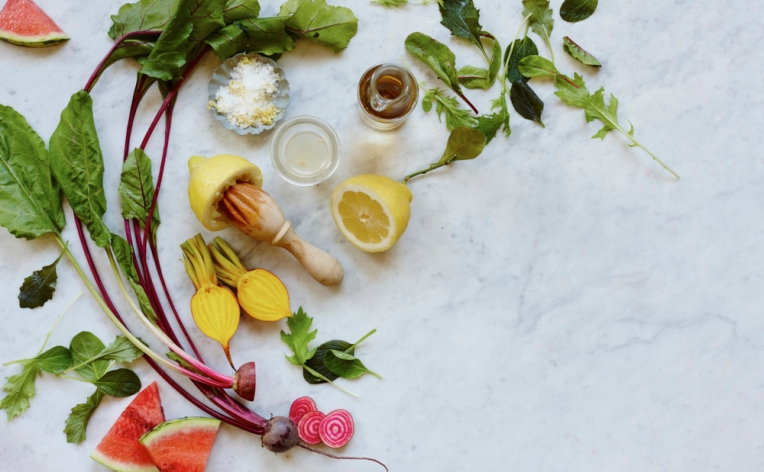 Overhead photography of various salad ingredients including beetroot, mixed leaves, lemons and watermelon.
