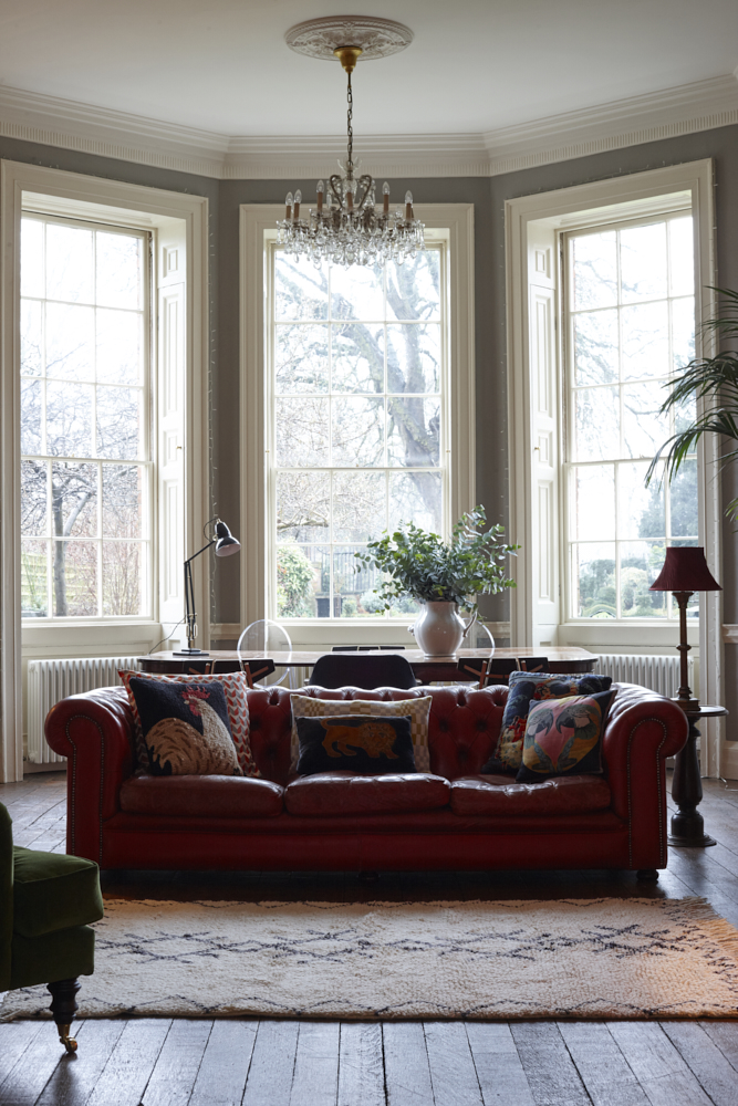 Margot Selby cushions on a red leather sofa. Berber rug. Interiors photographer Joanna Henderson