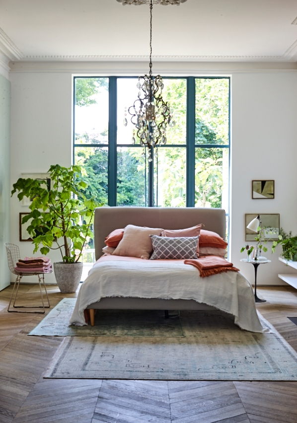 Bed with blush pink bed linen cushions and pillows on a parquet floor with green plantpot. Interiors photography by Joanna Henderson