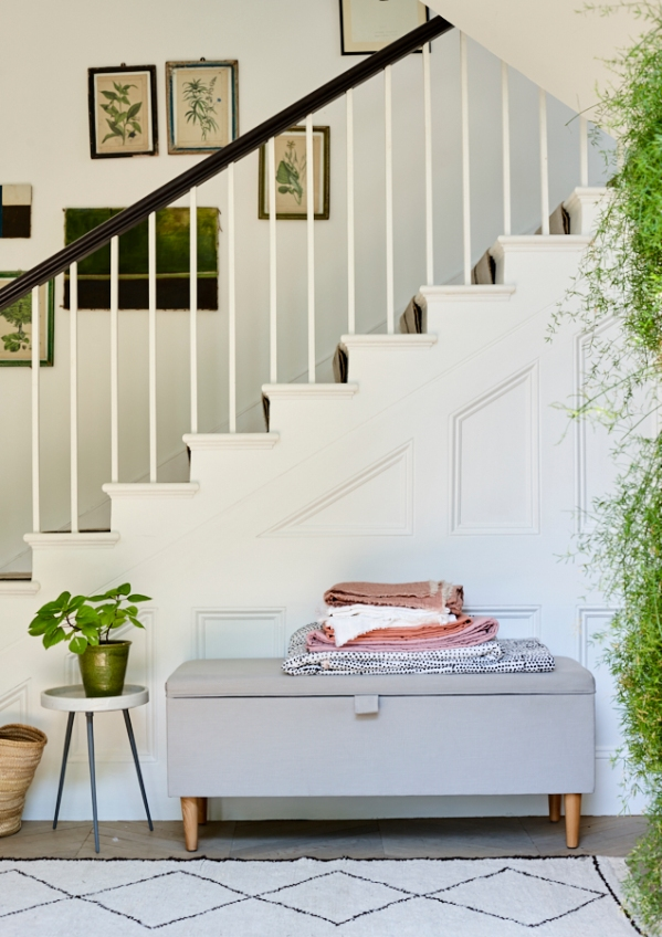 Blanket box with white staircase, blush pink blankets and greenery. Still life photography by Joanna Henderson
