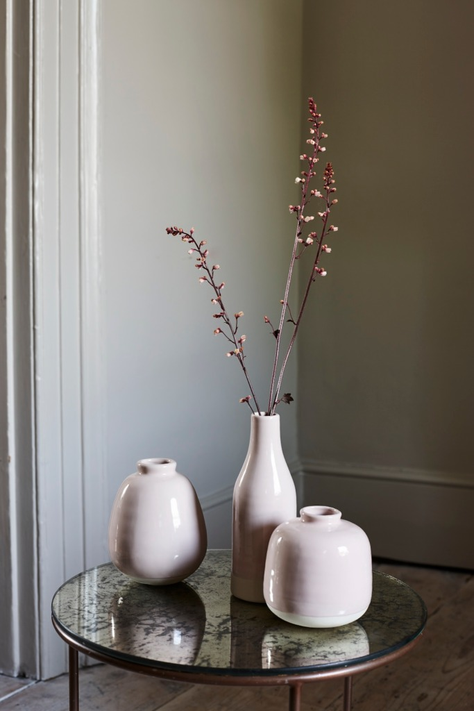 Pastel pink vases in various shapes on a mirrored table