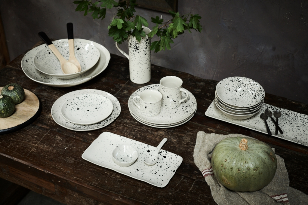 Black and white paint speckled ceramics on a dark wooden table with seasonal squashes