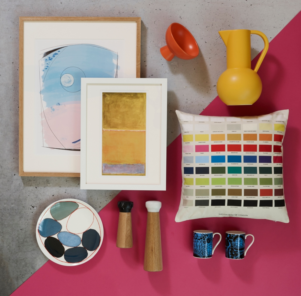 Framed prints, ceramics, salt and pepper pots and multi coloured cushion on a bright pink background