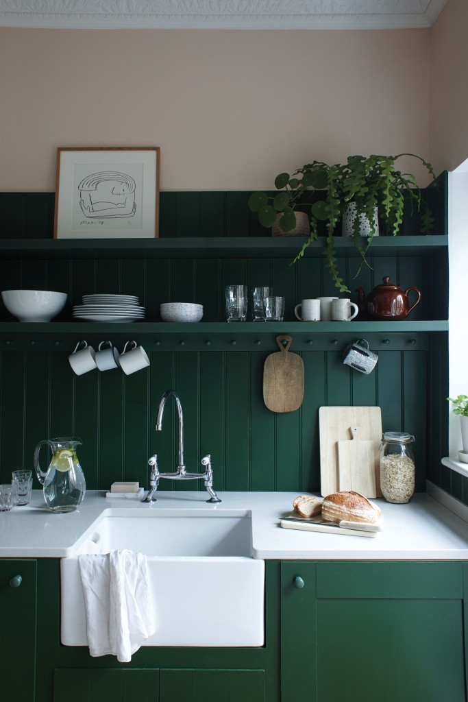 Farrow and Ball Kitchen worktop and sink area painted in green and pink with a selection of glasses, crockery and plants